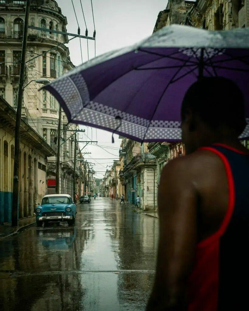 Fotografie Tipps - Jörg Nicht - Kuba -Person auf der Straße mit Regenschirm - Auto